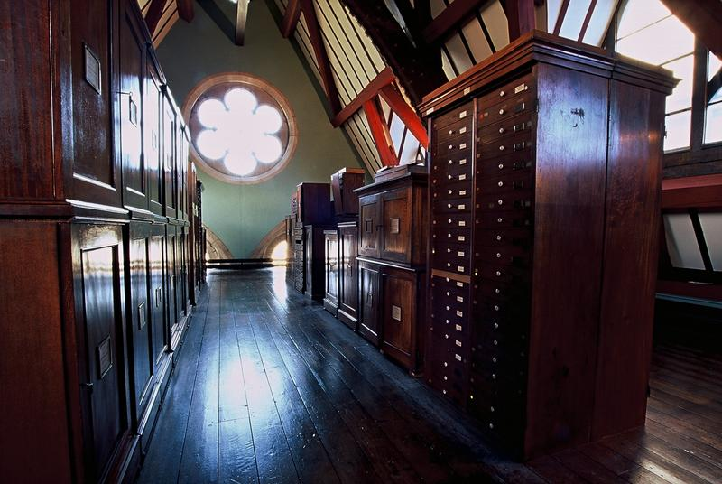 Photograph of wooden-beamed and wooden-floored room with bright light emerging through flow-shaped window in back hall. In the room are dark wooden museum cabinets of drawers.